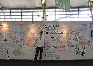Chris SHipton standing in front of a trade show booth that has been fully illustrated